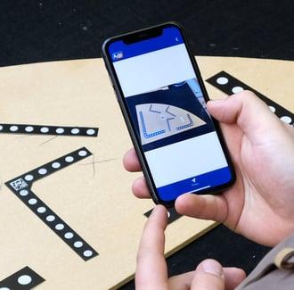 Pracownik skanuje szablony za pomocą swojego smartfonu i A+W iShape.
